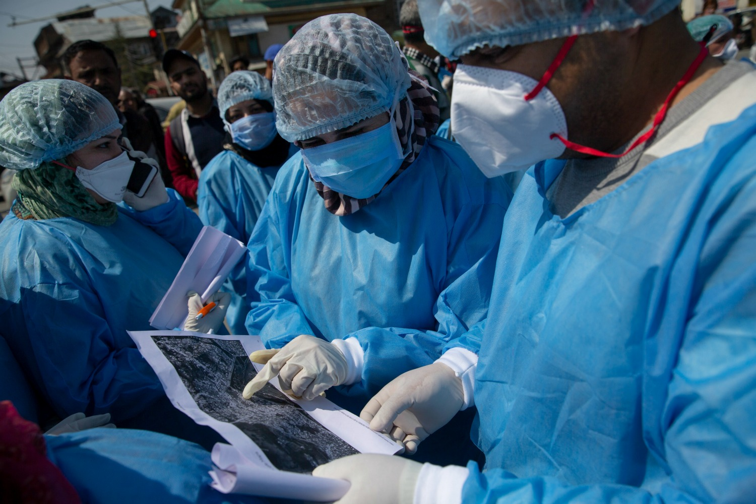 Kashmiri doctors looks at an aerial map.