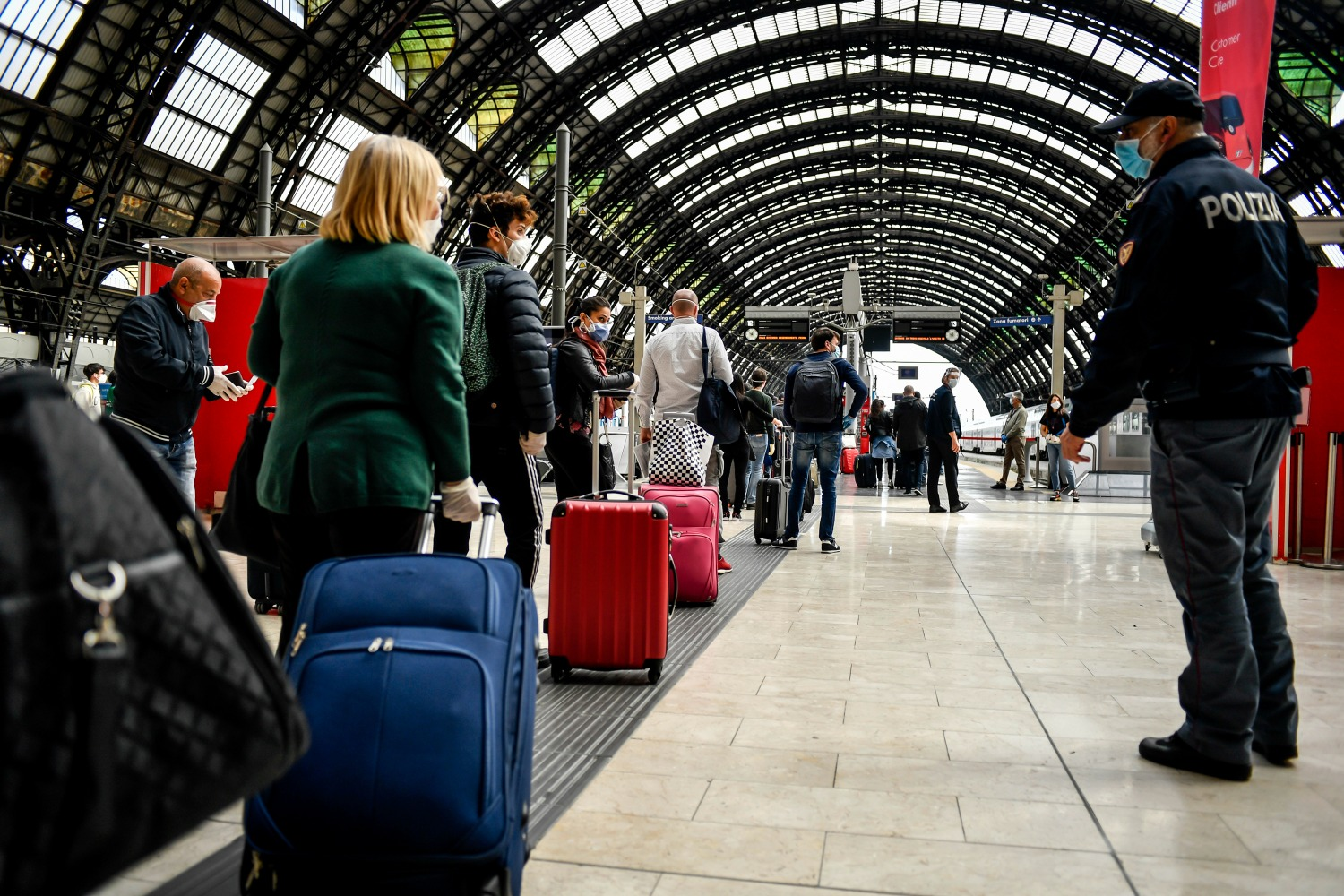 People line up to board the train in Milan, Italy.
